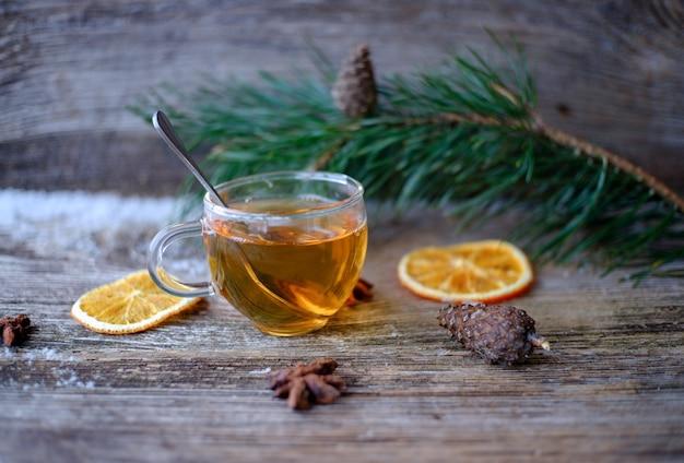 松の枝、乾燥したオレンジ、松ぼっくり、アニスの星と雪と木製のテーブルの上のガラスカップと緑茶