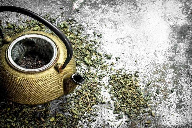 ティーポット付きの緑茶。素朴な背景に。
