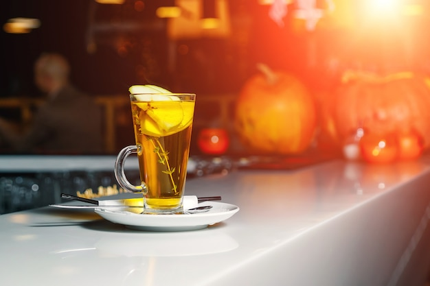 Green tea with apple slices in a glass cup on a white bar counter