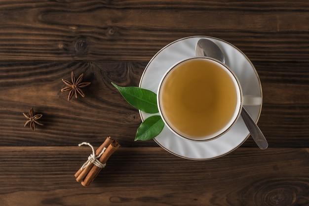 흰색 세라믹 컵에 있는 나무 테이블에 계피를 넣은 녹차. 정상에서 본 모습. 건강에 도움이 되는 상쾌한 음료.