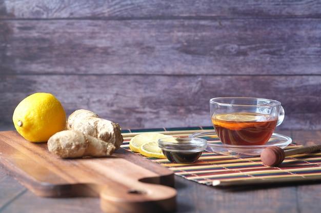 Зеленый чай с имбирем, лимоном и медом на деревянных фоне