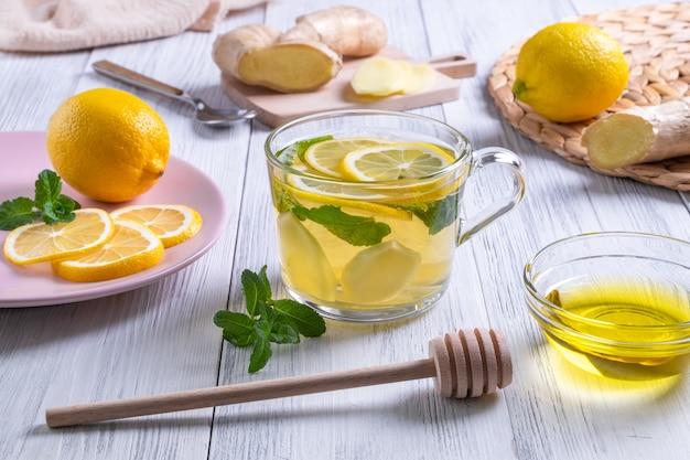 Зеленый чай с лимонным имбирем и медом в стеклянной чашке с апельсинами на деревянном столе