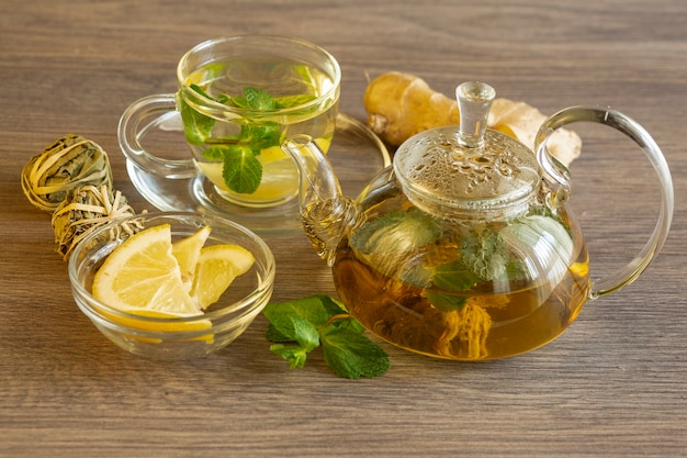 나무 테이블에 레몬, 생강, 민트가 들어간 녹차. 비타민과 항산화 성분이 풍부한 건강 식품.