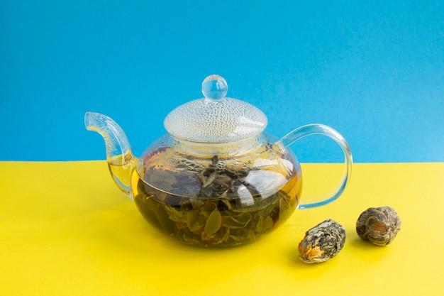 ガラスのティーポットに蓮の花が入った緑茶。閉じる。スペースをコピーします。