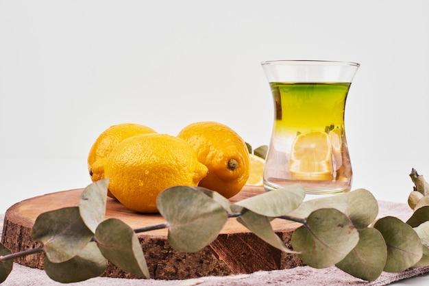Tè verde con tre limoni su superficie bianca con foglie.