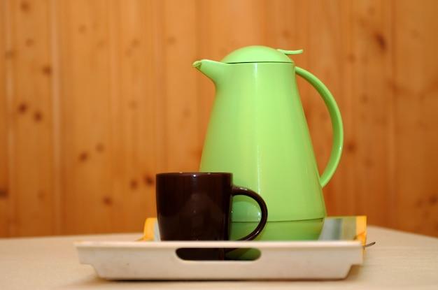 緑のティーポットとトレイ上のカップ。