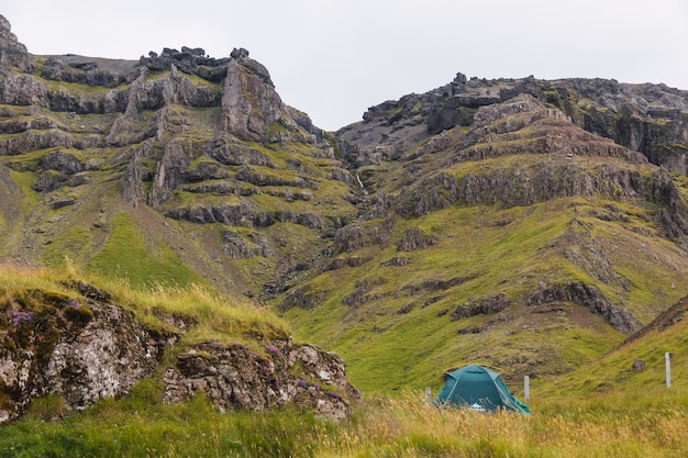丘のふもとにあるアイスランドの緑のテント。アイスランドでのキャンプ