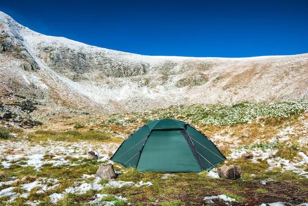 Зеленая палатка в снежных горах. красивый весенний пейзаж