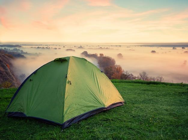 Зеленая палатка на холме над туманной рекой