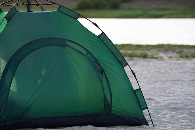 川を背景に砂浜の緑のテント。キャンプ、トレッキング、ハイキング。