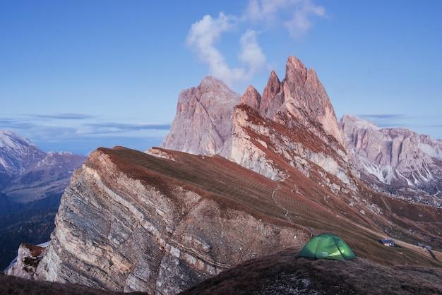 丘の上に立っている緑のテント。セセダのアルプスの素晴らしい場所。