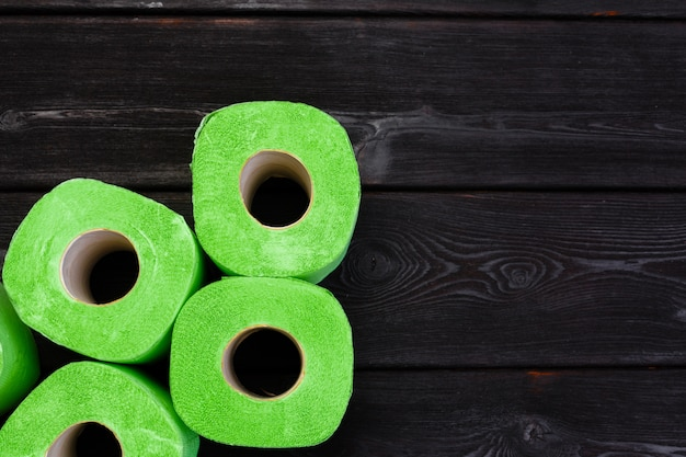 Green toilet paper rolls on black wooden table