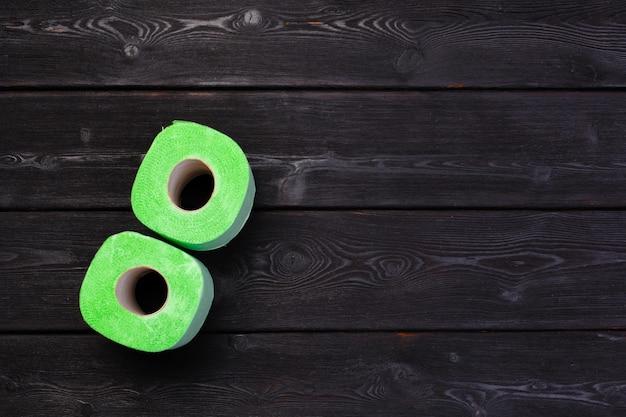 Green toilet paper rolls on black wooden