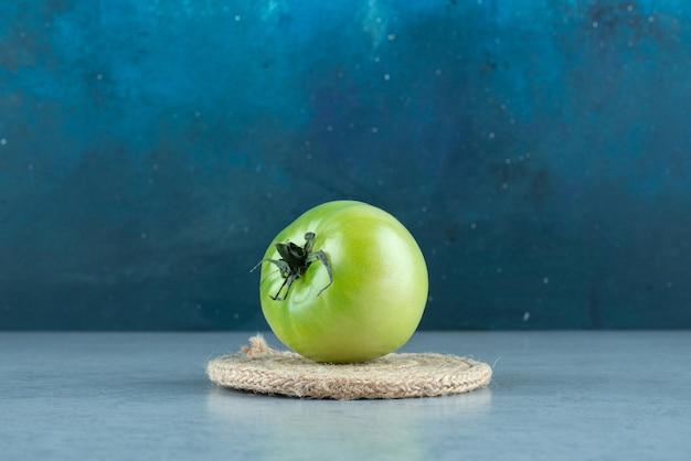 Зеленый помидор с веревкой на мраморе.