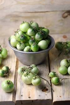 Green tomatoes in a bowl on a wooden surface.