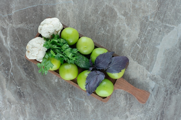 Green tomatoes and cauliflower pieces topped with amaranth and parsley leaves on a tray on marble.