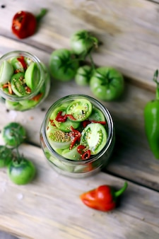Green tomatoes in jars on a wooden surface.