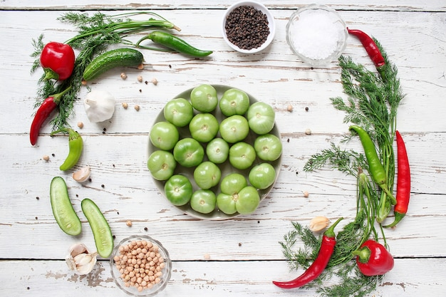 Green tomatoes, pickles on white wooden table with green and red and chili peppers, fennel, salt, black peppercorns, garlic, pea, close up, healthy concept, top view, flat lay