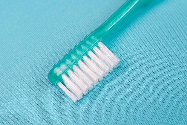 青いテーブルの上の緑の歯ブラシ
