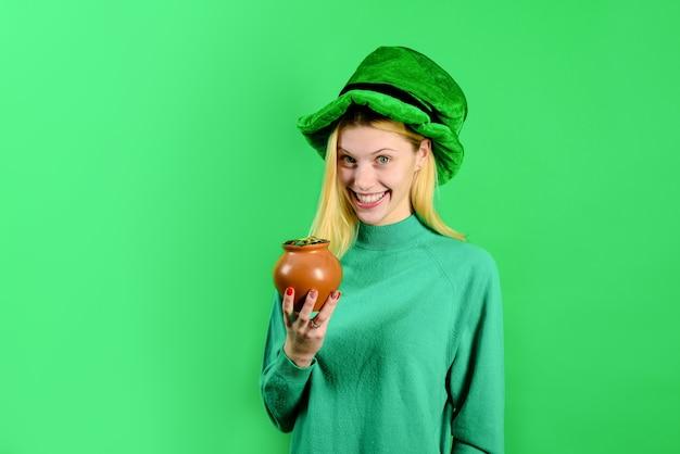 緑のシルクハットのブロンドの女の子は、金のレプラコーンと鍋を保持します緑のシルクハット緑のシルクハット