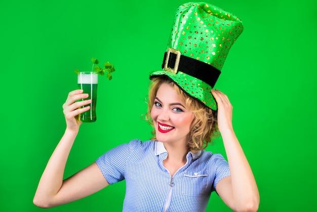 緑のシルクハット聖パトリックの日聖パトリックの日シルクハットの女性は緑のビールレプラコーングリーンを保持します
