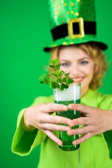 緑のシルクハット聖パトリックの日女性の緑のシルクハットはビールレプラコーングリーンビールとガラスを保持します
