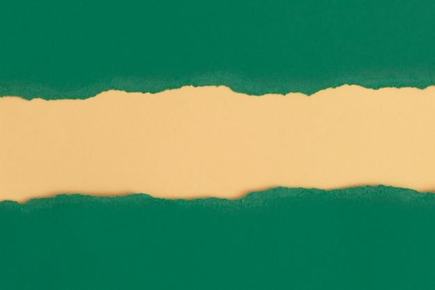 黄色の背景を持つテキストのためのスペースと緑の破れた紙