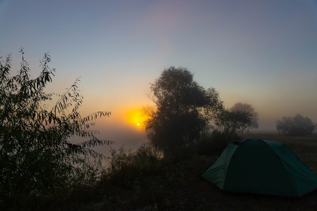 Green tourist tent by the river at sunrise, with morning autumn fog on the water. outdoor tourist landscape.