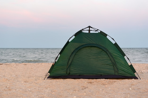Green tourist tent on the sandy beach