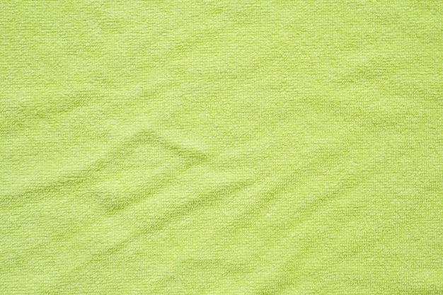 緑のタオル生地のテクスチャ表面は背景をクローズアップ