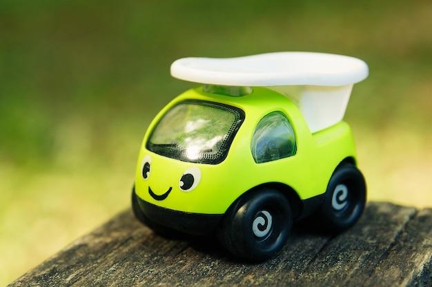 笑顔の屋外の緑のおもちゃの車をクローズアップ