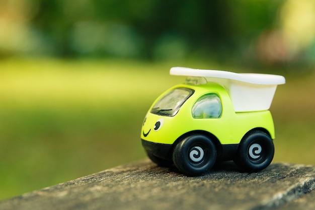 屋外の笑顔で緑のおもちゃの車