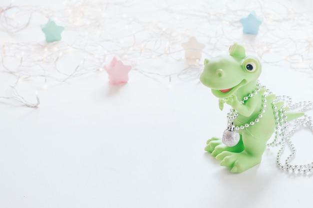 크리스마스 트리로 녹색 장난감 공룡입니다. 크리스마스 장식으로 귀여운 작은 공룡 프리미엄 사진