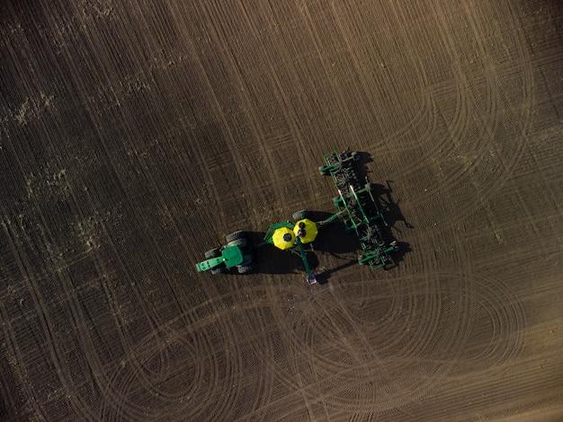 Зеленый трактор с посевным комплексом в поле вид сверху