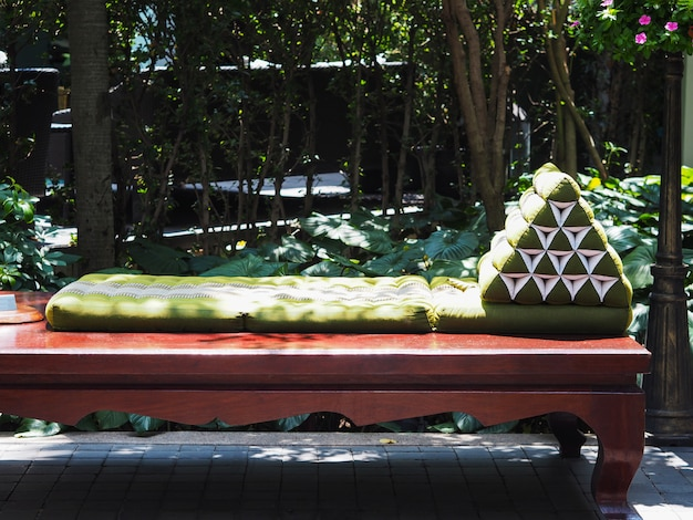 木製のベッドの上の緑の伝統的なタイの三角形の枕