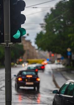 Зеленый светофор во время дождя, автомобили проезжают мимо