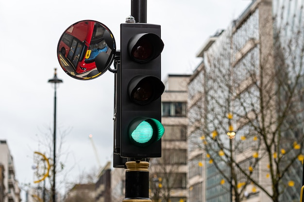 Green traffic light signal and traffic convex mirror with the reflection of the red bus