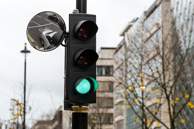Green traffic light signal and traffic convex mirror with the reflection of the vehicle, london, england, uk