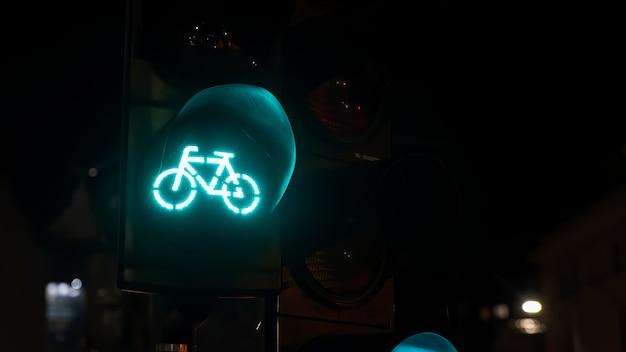 Зеленый светофор с логотипом велосипеда на нем ночью в бухаресте, румыния