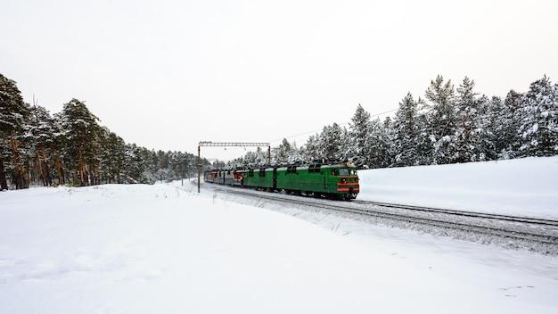 녹색 기차는 기차 개념으로 여행하는 겨울 숲을 통과합니다.