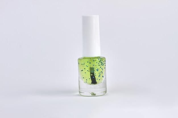 白で隔離される緑の透明なマニキュア。メイクアップ商品のクローズアップ。