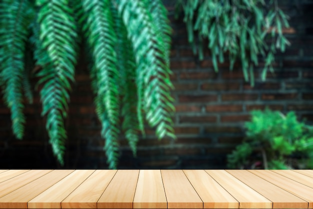 The green trees against walls.wooden board empty table in front of blurred background.