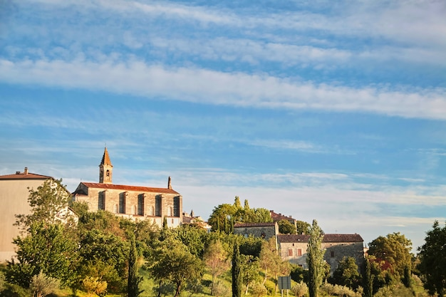 Barjac-프랑스 남부의 종탑이있는 푸른 나무와 건물 및 교회