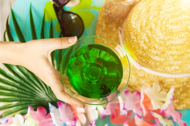 Green tropical cocktail and hand