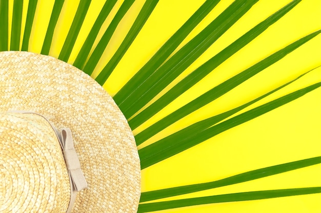 Green tropical palm leave, hat on bright yellow . minimal summer concept. creative flat lay. close up. selective focus. copy space