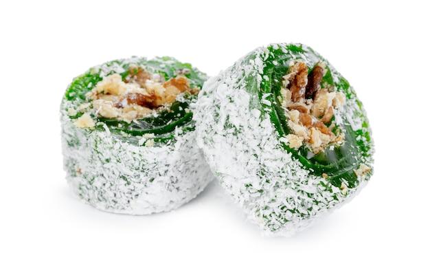 Зеленый рахат-лукум с орехами на сахарной пудре, изолированные на белом фоне