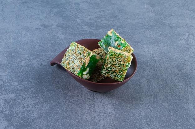 Зеленые лукумы в миске на мраморной поверхности