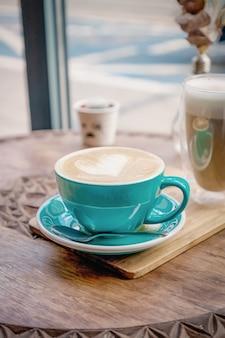 Зеленая бирюзовая чашка кофе капучино с сердцем на деревянном столе в кафе