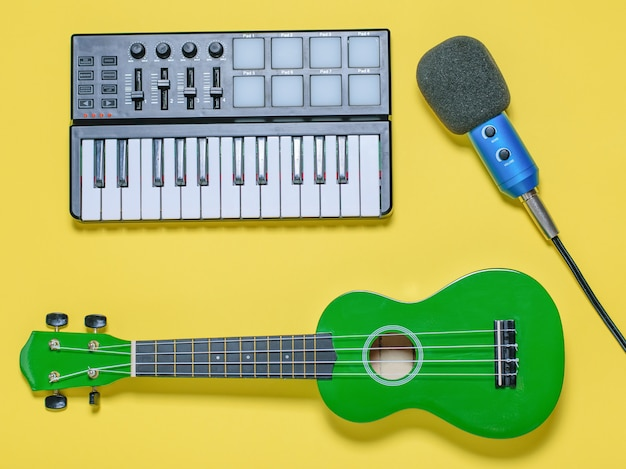 Green ukulele, blue microphone with wires and music mixer on yellow surface. the view from the top.