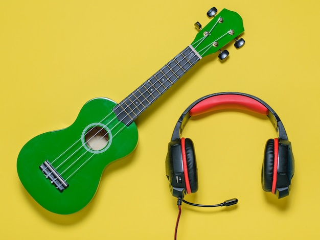 Green ukulele guitar and red-black headphones on yellow background. the view from the top.